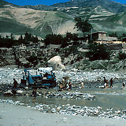 21 May 1976<br /> A flash flood washed down boulders onto the road, creating a temporary dam.<br /> Russian-made bulldozer brought in to clear the boulders was the only bulldozer in Badakhshan. South section houses in background.