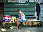 14 OCTOBER 2015 - BANGKOK, THAILAND:  A man who is being evicted from the neighborhood around Wat Kalayanamit cuts up pomelo, which he sells door to door. Fifty-four homes around Wat Kalayanamit, a historic Buddhist temple on the Chao Phraya River in the Thonburi section of Bangkok, are being razed and the residents evicted to make way for new development at the temple. The abbot of the temple said he was evicting the residents, who have lived on the temple grounds for generations, because their homes are unsafe and because he wants to improve the temple grounds. The evictions are a part of a Bangkok trend, especially along the Chao Phraya River and BTS light rail lines. Low income people are being evicted from their long time homes to make way for urban renewal.         PHOTO BY JACK KURTZ