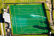 A sprinkler waters Astroturf, surrounded by grass, at Jordan Field. Watering the artificial turf lends it a more controllable surface for field hockey matches.  A fine mist evaporates from this large sprinkler before it even reaches the ground, representing wasted water.