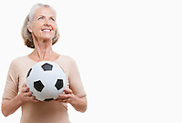 Smiling senior woman in casuals holding soccer ball against white background
