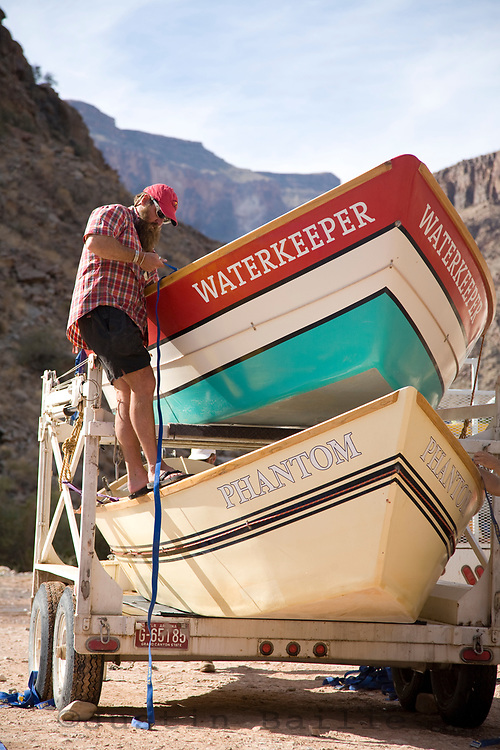 River guide strapping down dories on the Grand Canyon. Grand Canyon NP, AZ.