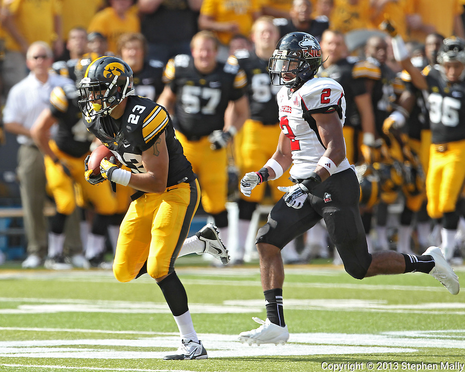 August 31 2013: Iowa Hawkeyes wide receiver Jordan Cotton (23) runs after a catch as Northern Illinois Huskies cornerback Sean Evans (2) gives chase during the second quarter of the NCAA football game between the Northern Illinois Huskies and the Iowa Hawkeyes at Kinnick Stadium in Iowa City, Iowa on August 31, 2013. Northern Illinois defeated Iowa 30-27.