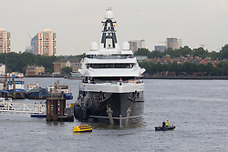 © Licensed to London News Pictures. 04/07/2018. London, UK.  The new 243 feet long superyacht, Elandess arrives in London for the first time ever on the River Thames and moors  at HMS President, the Royal Navy Reserve Unit next to St Katharine Docks and Tower Bridge this evening. Elandess was built at the Abeking and Rasmussen shipyard in Germany, launched in May 2018 and has just completed sea trials ahead of its London visit. Elandess has an axe-bow, dark hull and low-slung superstructure. There are a variety of entertaining communal spaces, from the 8 x 2.5-metre superyacht swimming pool located on the massive sun deck to the Nemo Lounge with portholes below the waterline and an observation lounge on the upper deck. Guest accommodation includes six staterooms, including the master suite which is placed forward on the main deck with an observation lounge directly above on the upper deck.  Photo credit: Vickie Flores/LNP
