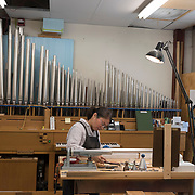 Nomi Hamada works on pipes for an organ being built by CB Fisk, of Gloucester, MA