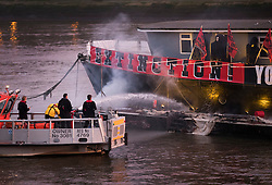 "© Licensed to London News Pictures. 26/11/2016. London, UK. A Fire Service riverboat extinguishes a fire started by Joe Corre, the son of former Sex Pistol manager Malcolm McLaren and Vivienne Westwood as he burns his personal collection of Sex Pistols punk memorabilia on a boat in the Thames in Chelsea. Earlier this week Joe Corre said that punk has become nothing more than a ""McDonald's brand ... owned by the state, establishment and corporations"". His collection is estimated to be worth £5 million. Photo credit: Peter Macdiarmid/LNP"