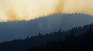 The sun sets behind a wildfire on Tepee Mountain in the Purcell Mountains during 2015 fire season. Yaak Valley, northwest Montana.