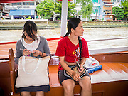 09 OCTOBER 2012 - BANGKOK, THAILAND:  A woman knits while another enjoys the view on a Chao Phraya Express Boat on the Chao Phraya River in Bangkok, Thailand. Boats and ships play an important in daily life in Bangkok. Thousands of people commute to work daily on the Chao Phraya Express Boats and fast boats that ply Khlong Saen Saeb. Boats are used to haul commodities through the city to deep water ports for export.       PHOTO BY JACK KURTZ