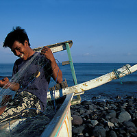 Indonesia, Bali, Fisherman repairs nets by outrigger canoe by Indian Ocean