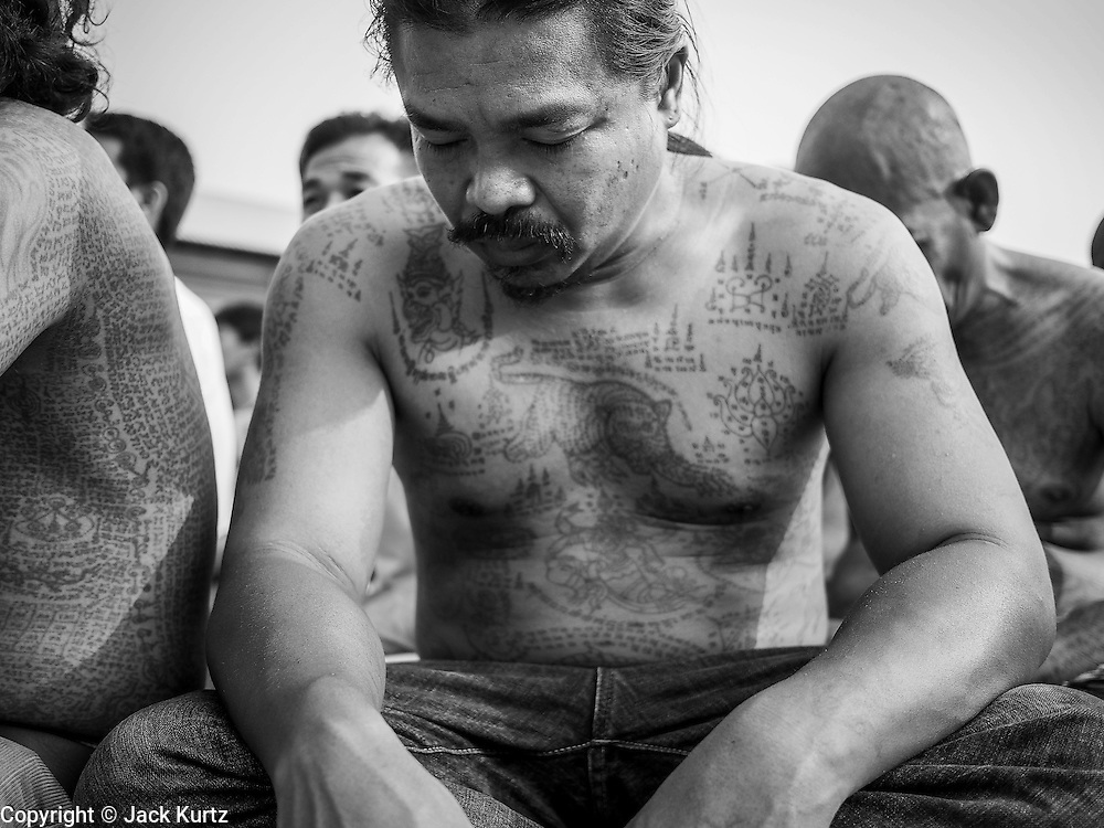 "15 MARCH 2014 - NAKHON CHAI SI, NAKHON PATHOM, THAILAND: A man covered in tattoos prays at the Wat Bang Phra tattoo festival. Wat Bang Phra is the best known ""Sak Yant"" tattoo temple in Thailand. It's located in Nakhon Pathom province, about 40 miles from Bangkok. The tattoos are given with hollow stainless steel needles and are thought to possess magical powers of protection. The tattoos, which are given by Buddhist monks, are popular with soldiers, policeman and gangsters, people who generally live in harm's way. The tattoo must be activated to remain powerful and the annual Wai Khru Ceremony (tattoo festival) at the temple draws thousands of devotees who come to the temple to activate or renew the tattoos. People go into trance like states and then assume the personality of their tattoo, so people with tiger tattoos assume the personality of a tiger, people with monkey tattoos take on the personality of a monkey and so on. In recent years the tattoo festival has become popular with tourists who make the trip to Nakorn Pathom province to see a side of ""exotic"" Thailand.   PHOTO BY JACK KURTZ"