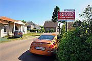 Duitsland, Elten, 15-6-2010In Elten, gemeente Emmerich vlak over de grens bij Arnhem en Zevenaar, staan vele nieuwe huizen die gebouwd en bewoond zijn door nederlanders. Een oranje auto staat voor een woning die verkocht moer worden.Nederlandse makelaars zijn aktief in deze markt. Duitsers klagen over de gebrekkige integratie, deelname aan het maatschappelijke en sociale leven, van de Hollanders. Verschillenden hebben hun huis alweer verkocht en zijn teruggegaan. Ook vinden er nogal wat echtscheidingen plaats. Het bouwen van een huis en de bouwkavel zijn goedkoper als in Nederland.Foto: Flip Franssen/Hollandse Hoogte