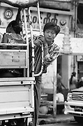 Traveller hangs from the back of  abus as it rides through Rangoon. Burma 1999