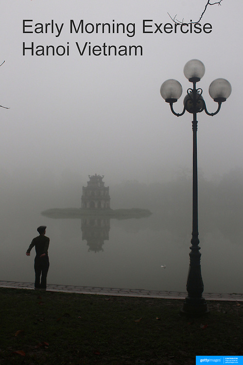 An elderly Vietnamese gentleman stretches on a misty morning beside Hoan Kiem Lake, Hanoi, with the Thap Rue Pagoda visible through the mist.. For a county not know for it's sporting prowess, Hanoi, Vietnam's capital, appears to be gripped in a fitness frenzy. Before 6am street corners, parks and lake sides are a hive of activity as keep fit classes, Tai chi and personal exercise regimes are seen in abundance around the city. Particularly noticeable are Women's keep fit classes, often accompanied by loud poor quality western disco beat music as the occupants of the city get fit come rain or shine. Hanoi, Vietnam. 17th March 2012. Photo Tim Clayton