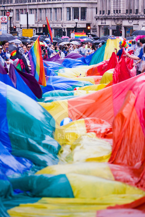London, June 28th 2014. A 100 yard long rainbow flag is drawn along Regent Street as the Pride London parade proceeds through the city's streets.