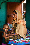 """Shashi Devi (aged 28, right) and her brother-in-law's wife Monika Devi (22, background) in their house in the village of Shahpurjat, Ghaziabad, Uttar Pradesh, India. While Shashi had a tubectomy done after having 2 sons, Monika is still trying for a son after having 2 daughters. Shashi did the operation because she wanted to """"give her 2 children the best and inflation will make things difficult"""", and she believes that a """"small family = happy family"""". She has been pushing Monika to get her husband to do an NSV so that Monika's life is not endangered since her previous pregnancies have been complicated. Photo by Suzanne Lee / Panos London"""