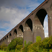 The arches of the Conisbrough Railway Viaduct Bridge with a rain cloud passing in South Yorkshire, England