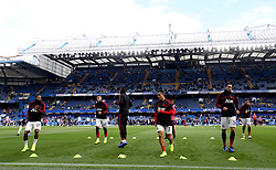 Manchester United players warm up prior to the beginning of the match