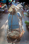 Vietnamese woman carrying chickens in basket