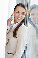 Beautiful businesswoman answering cell phone by window in office
