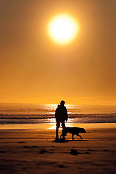 © Licensed to London News Pictures. 12/03/2012. Bamburgh, UK. A dog walker on Bamburgh Beech at sunrise in Northumberland, North East England on March 12th, 2012. Photo credit : Ben Cawthra/LNP.
