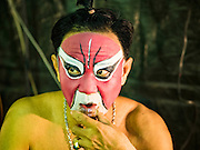 15 OCTOBER 2015 - BANGKOK, THAILAND:  A Chinese opera performer relaxes and drinks tea backstage before an opera performance at the Vegetarian Festival at the Joe Sue Kung Shrine in the Talat Noi neighborhood of Bangkok. The Vegetarian Festival is celebrated throughout Thailand. It is the Thai version of the The Nine Emperor Gods Festival, a nine-day Taoist celebration beginning on the eve of 9th lunar month of the Chinese calendar. During a period of nine days, those who are participating in the festival dress all in white and abstain from eating meat, poultry, seafood, and dairy products. Vendors and proprietors of restaurants indicate that vegetarian food is for sale by putting a yellow flag out with Thai characters for meatless written on it in red. The shrine is famous for the Chinese opera it hosts during the Vegetarian Festival. The operas are free.   PHOTO BY JACK KURTZ