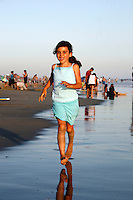 21 June 2008:  Taylor Brown runs along the water line near the surf at the beach during summer at tower 9 in Huntington Beach, CA.
