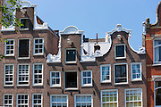 Canalside quaint ornate gabled houses - Dutch gables - on Herengracht in Jordaan District of Amsterdam, Holland