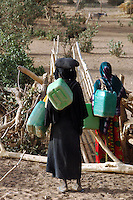 Niger, Agadez, Tidene, 2007. Women enter the garden compound. They will buy or trade for vegetables and carry back as much water as possible.