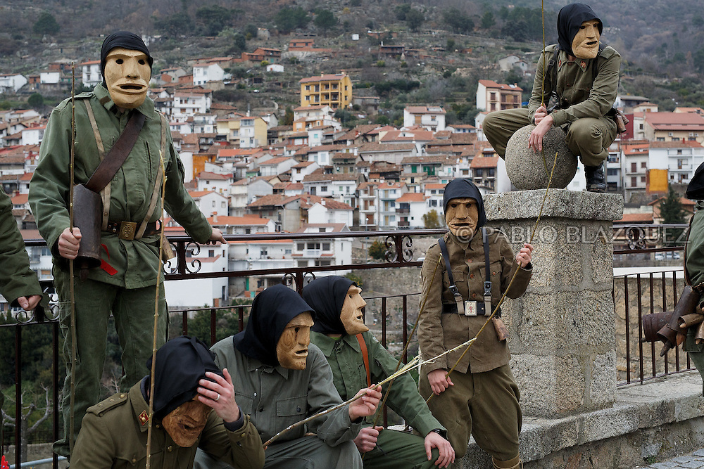 The Machurreros from Pedro Bernardo sit in a park during Carnival on February 6, 2016 in Pedro Bernardo, in Avila province, Spain. The origins of this pagan festival are unknown. The Machurreros wear wood masks, a military dress, black handkerchief, cowbells, and hold wicker stick. The festival disappeared after Dictator Franco forbid carnival festivals in 1937, but it was recently recovered. Before disappearing, male villagers after the military service, used to dress as Machurreros as they run along the streets scaring children and adults with their wicker stick to bring fertility to the land and expel the evil spirits. (© Pablo Blazquez)