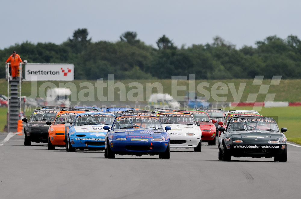 Adam Gore (green car) leads Andrew Wright into Riches Corner at the start of one of the rounds of the 2011 Ma5da Racing MX5 Mk1 Championship at Snetterton.