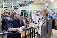 """Garden City, New York, USA. March 9, 2019.  L-R, Carousel operator ANDREW OBERGH and Nassau County Executive LAURA CURRAN talk at railing around Nunley's Carousel, during Unveiling Ceremony of mural of a Nunley's Carousel horse. Obergh's family runs the carousel, and raised $85,000 for """"Pennies for Ponies"""" campaign to help restore the horses. Event was held at historic Nunley's Carousel in its Pavilion on Museum Row on Long Island."""