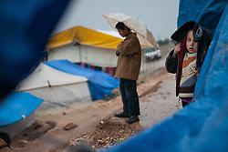 A displaced child looks to the camera covering with her jacket in the midst of a heavy rain  in Qah's refugee camp, February 6th, Idlib, Syria....Situated 7 km away from the Turkish border Qah refugee camp is one of the three refugee camps in the area -inside Syria's territory- with an estimated number of 3,200 refugees and growing by the day. Build in August 2012 by the help of Libyan al-Yosser charity and with the provision of tents, blankets etc of the Syrian National Council., Syria, February 6, 2013. Photo by Daniel Leal-Olivas / i-Images.