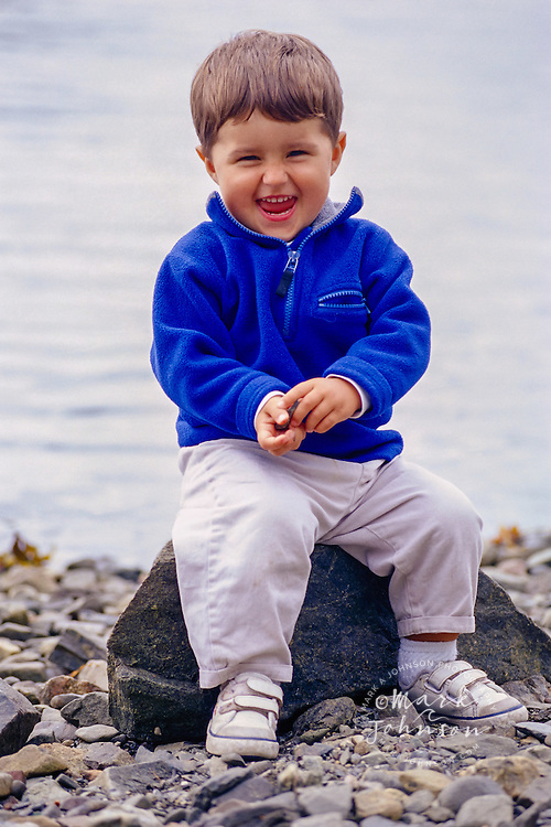 Happy Toddler Playing with Pebbles on Beach