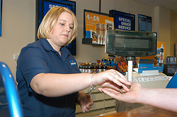 Young woman working in Blockbuster video rental shop serving a customer; Merseyside