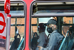 © Licensed to London News Pictures. 15/06/2020. London, UK. A man wearing a face covering travels on a bus in north London. Face covering is now compulsory on buses, trains, trams and planes. Secretary of State for Transport, Grant Shapps has said that, people who do not wear face covering on public transport from today could be fined up to £100. Photo credit: Dinendra Haria/LNP