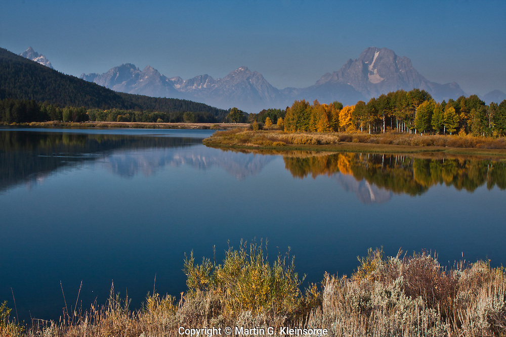 Reflections of 12,605 ft. Mount Moran in Oxbow Bend on the Snake River.  The smoky haze is caused by a near by wild fire.  Grand Teton National Park, Wyoming, USA.