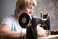 Mature woman works at sewing machine