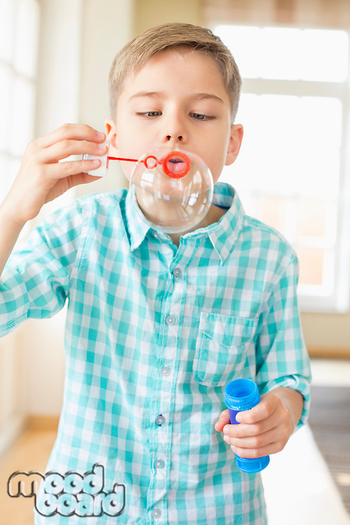 Cute boy playing with bubble wand at home