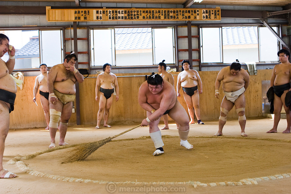A wrestler tidies up the ring during break in practice for a tournament in Nagoya, Japan.