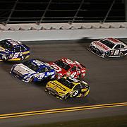 NASCAR Sprint Cup drivers Marcos Ambrose (9), Carl Edwards (99) and Martin Truex Jr. (55) run three wide in turn four of the NASCAR Sprint Unlimited Race at Daytona International Speedway on Saturday, February 16, 2013 in Daytona Beach, Florida.  (AP Photo/Alex Menendez)