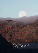 December's full moon known as the Cold Moon, sets over the mountains in Baja California, Mexico.