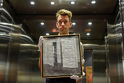 "© Licensed to London News Pictures. 02/06/2017. London, UK.   A technician presents ""White Doors"", 1899, by Vilhelm Hammerhøi (Est. GBP 400-600k).  Preview of Sotheby's sale of 19th century European paintings which takes place on 6 June 2017 at Sotheby's in New Bond Street. Photo credit : Stephen Chung/LNP"