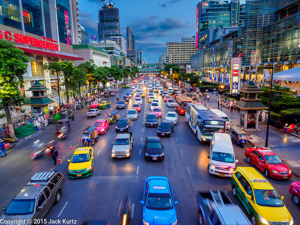 20 MAY 2015 - BANGKOK, THAILAND: Traffic on Ratchadamri Road passes between two large shopping complexes, a Big C Supercenter, on the right, and CentralWorld, a high end mall, on the left. Bangkok's malls consume more electricity than some provinces. Siam Paragon, a popular high end mall in central Bangkok, consumes nearly twice as much electricity at the northern province of Mae Hong Son. Thais and foreigners alike flock to the malls in Bangkok, which are air conditioned. Most of the electricity consumed in Bangkok is generated in Laos and Myanmar. In 2013, the Bangkok Metropolitan Region consumed about 40 per cent of the Thailand's electricity, even though the BMR is only 1.5 per cent of the country's land area and about 22 per cent of its population.   PHOTO BY JACK KURTZ