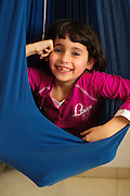 Happy and excited young girl of six in a hammock