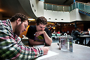 Alexander Reilly and William Clark look over some electrical engineering coursework in the atrium of the Academic and Research Center. Students often come to the atrium to study or get a meal from the atrium coffee shop. Photo by Ross Brinkerhoff.
