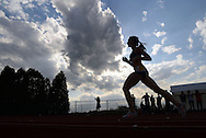 WARMINSTER, PA - MAY 1: A runner is silhouetted in clouds as she competes in the 1600 meter race during the Montgomery Memorial Track and Field Meet May 1, 2014 at William Tennent High School in Warminster, Pennsylvania. (Photo by William Thomas Cain/Cain Images)