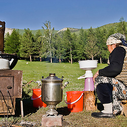 Woman doing domestic tasks outside her yurt near Karakol, Kyrgyzstan.