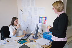 Young woman sitting at her desk talking to a colleague,