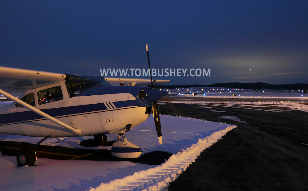 Montgomery, New York  - A single-engine plane is parked at Orange County Airport on Jan. 22, 2012. The runway lights are on in the background..