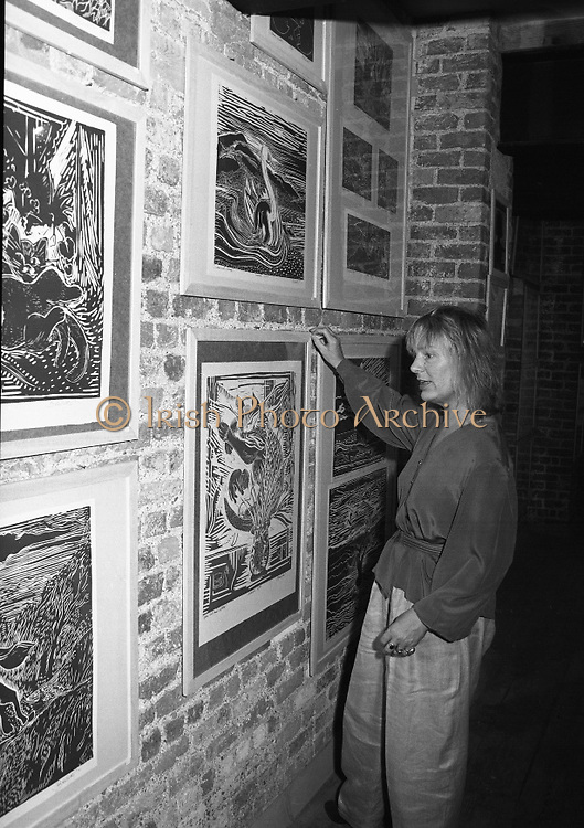 "Pauline Bewick Art Exhibition..1986..03.06.1986..06.03.1986..3rd June 1986..At the Guinness Hop Store,Dublin,artist Pauline Bewick is having an exhibition of her work.The exhibition called ""2 to 50 years""is a display of her work from age 2 to the present.the art work ranges from simple pencil sketches to more complex paintings and lino cuts...Photograph of the artist,Pauline Bewick,adjusting one of her lino cuts which is displayed on the wall of The hop Store,Dublin"