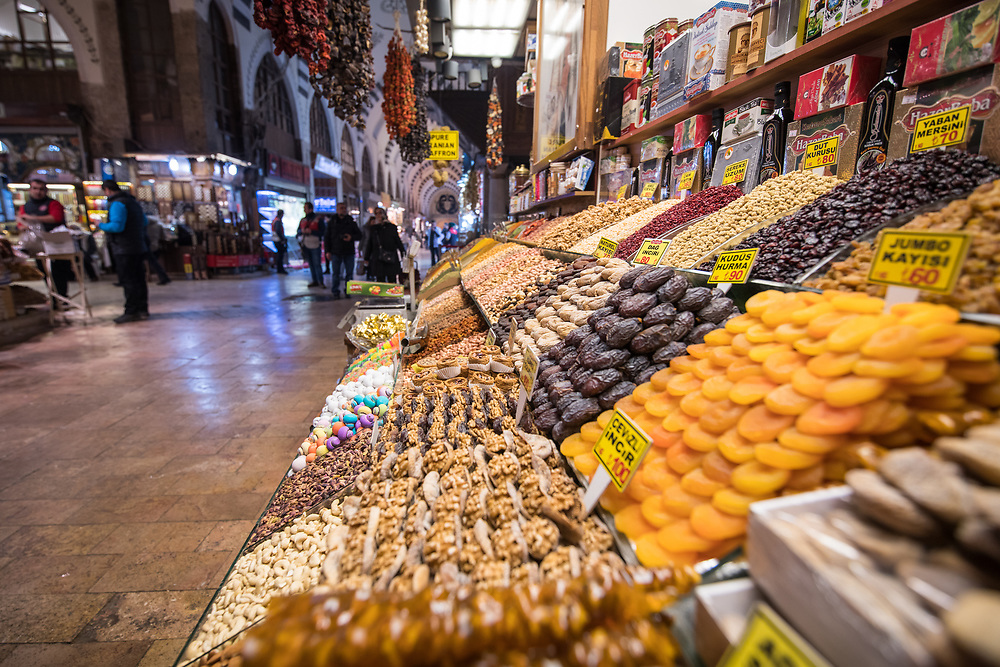 In front market stall at Istanbul Spice bazaar in Turkey are methodically stacked dried fruits and candies on display for customers to purchase